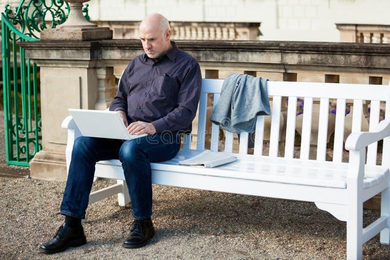 Bemannen Sie das Sitzen auf einer Bank unter Verwendung eines Laptops stockfoto