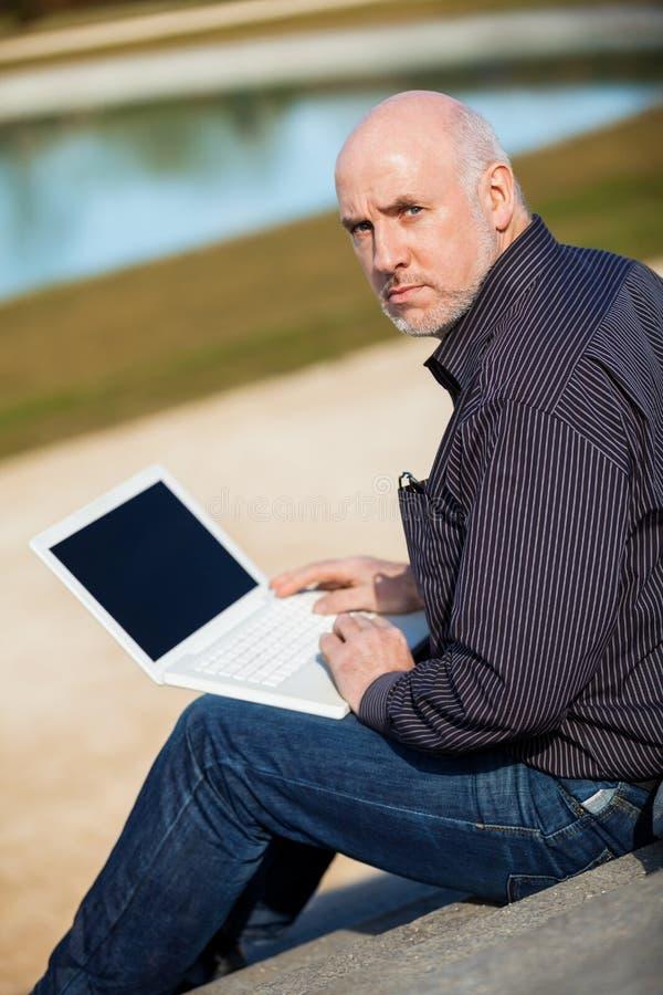 Bemannen Sie das Sitzen auf einer Bank unter Verwendung eines Laptops lizenzfreies stockbild