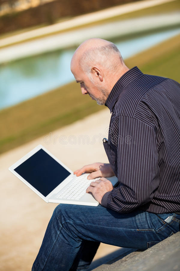 Bemannen Sie das Sitzen auf einer Bank unter Verwendung eines Laptops stockbild