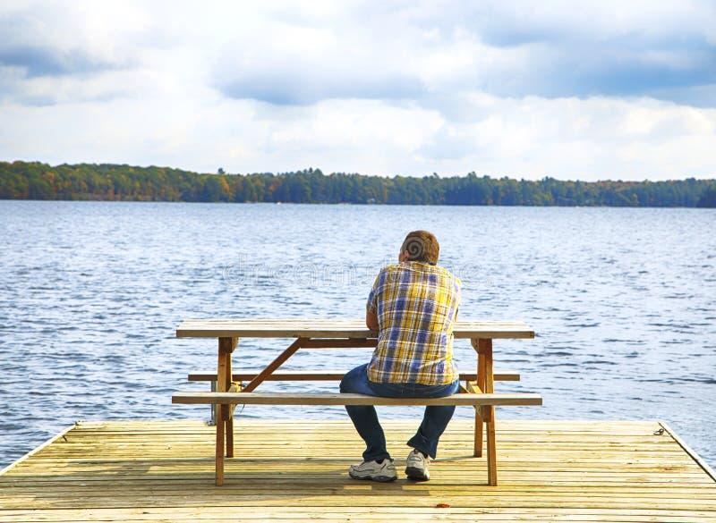 Bemannen Sie das Sitzen auf einer Bank vor einem See stockbild