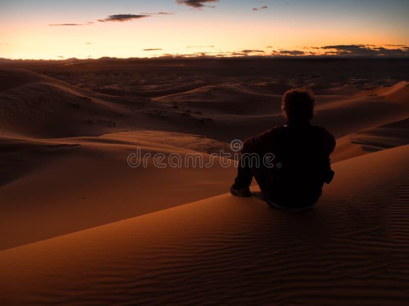 Bemannen Sie das Sitzen auf einer Düne in der Wüste beim Aufpassen des Sonnenuntergangs lizenzfreie stockfotos