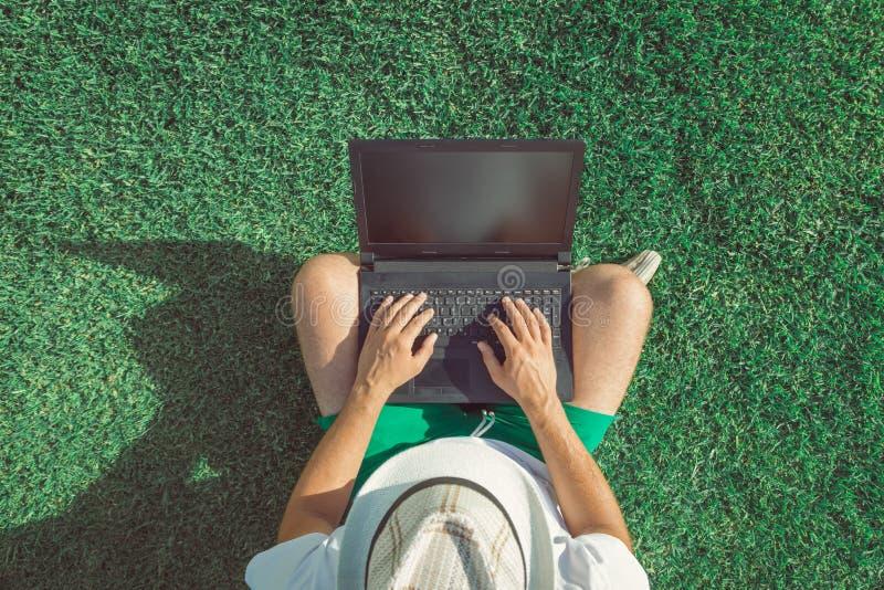 Bemannen Sie das Sitzen auf Gras und die Anwendung des Laptops des leeren Bildschirms stockbild