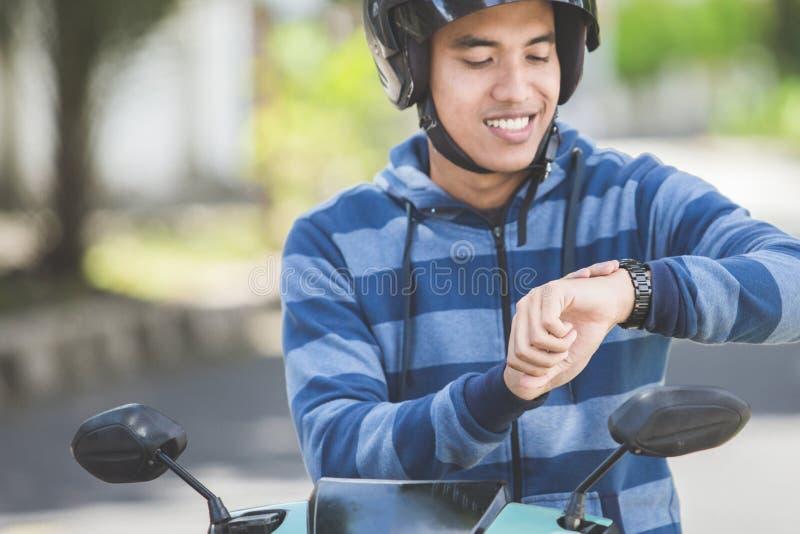 Bemannen Sie das Sitzen auf seinem Motorrad und das Betrachten seiner Uhr lizenzfreies stockfoto