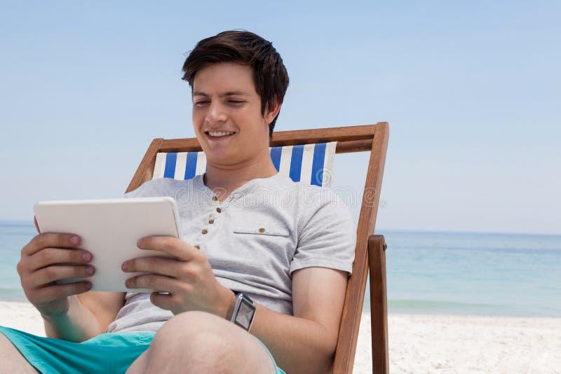Bemannen Sie das Sitzen auf sunlounger und die Anwendung der digitalen Tablette auf dem Strand lizenzfreies stockfoto