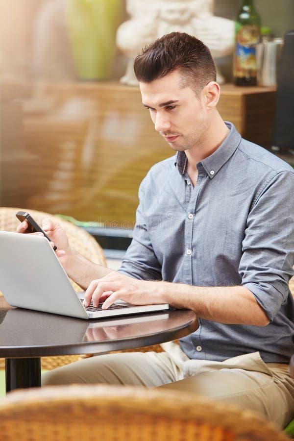 Bemannen Sie das Sitzen am Café mit Laptop und Handy stockfoto