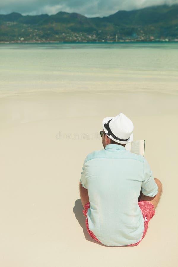 Bemannen Sie das Sitzen den exotischen Strand im Sommer allein, betrachtend während bezüglich lizenzfreie stockfotos