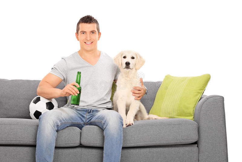 Bemannen Sie das Sitzen an der Couch mit seinem Welpen und Fußball stockfotografie