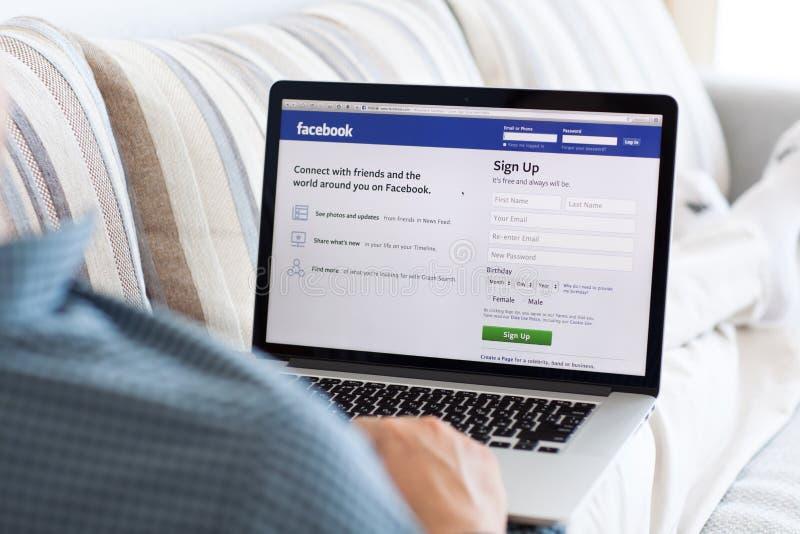 Bemannen Sie das Sitzen an der MacBook-Retina mit Standort Facebook auf dem scre stockfotografie