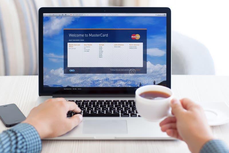 Bemannen Sie das Sitzen an der MacBook-Retina mit Standort MasterCard auf dem Sc stockfotos