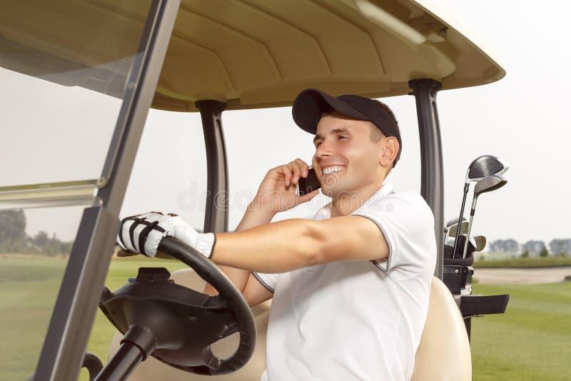 Bemannen Sie das Sitzen in einem Golfmobil und die Unterhaltung am Telefon lizenzfreie stockbilder