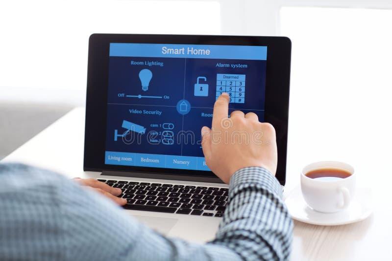 Bemannen Sie das Sitzen an einem Laptop mit dem intelligenten Haus des Programms lizenzfreies stockbild