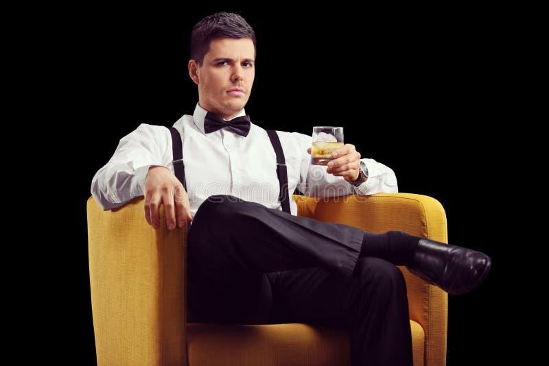Bemannen Sie das Sitzen in einem Lehnsessel und in einem trinkenden Whisky lizenzfreie stockfotos