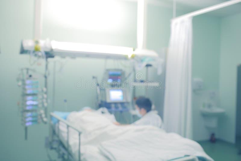 Bemannen Sie das Sitzen am geduldigen Kopfende in ICU, unfocused Hintergrund stockfoto
