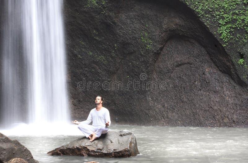 Bemannen Sie das Sitzen im Meditationsyoga auf Felsen am Wasserfall Tibumana stockbild