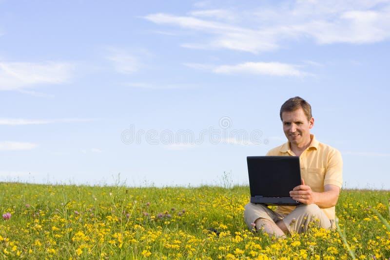 Bemannen Sie das Sitzen mit Laptop-Computer in einer Wiese lizenzfreie stockfotos