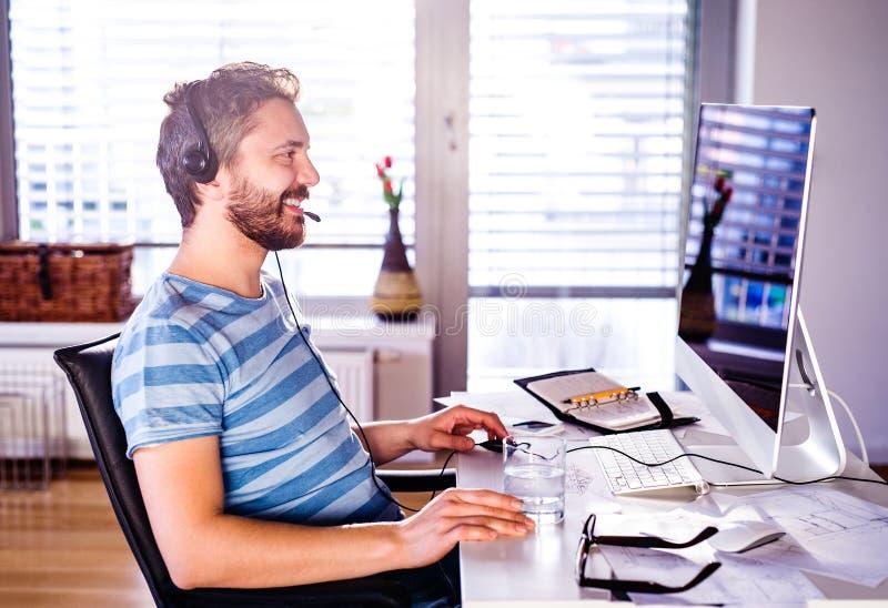 Bemannen Sie das Sitzen am Schreibtisch, der vom Haus auf Computer arbeitet stockbild