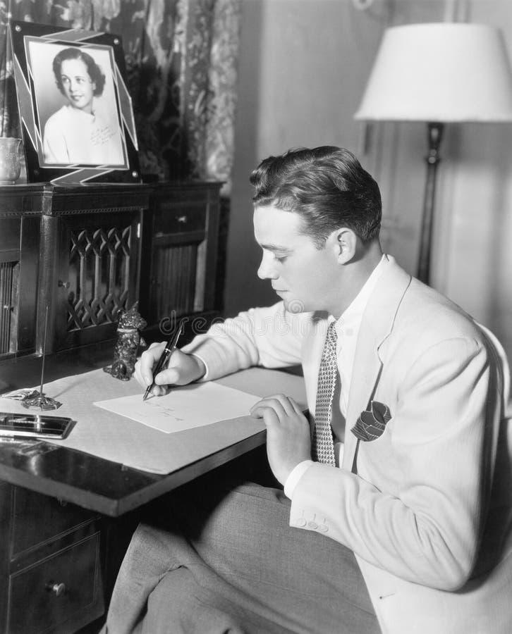 Bemannen Sie das Sitzen an seinem Schreibtisch, der einen Brief mit einem Füllfederhalter schreibt (alle dargestellten Personen s stockfotografie
