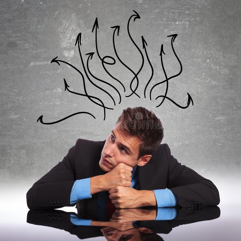 Bemannen Sie das Sitzen an seinem Schreibtisch mit seinem Verstand in allen Richtungen lizenzfreies stockfoto