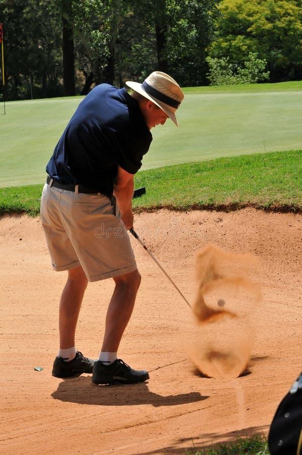 Bemannen Sie das Spielen des Golfschusses aus Sandbunker auf Grün heraus lizenzfreie stockfotos
