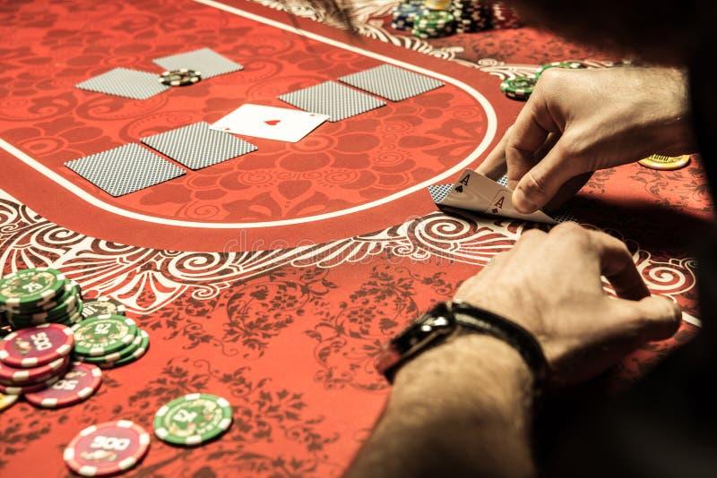 Bemannen Sie das Spielen des Pokers und das Betrachten von Assen auf Tabelle stockbilder