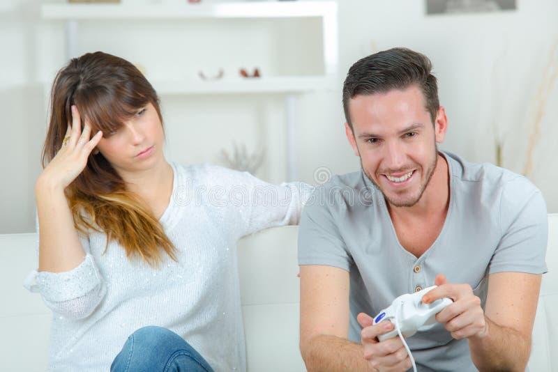 Bemannen Sie das Spielen von den Videospielen und von Freundin, die ihn betrachtend gebohrt wird stockbild