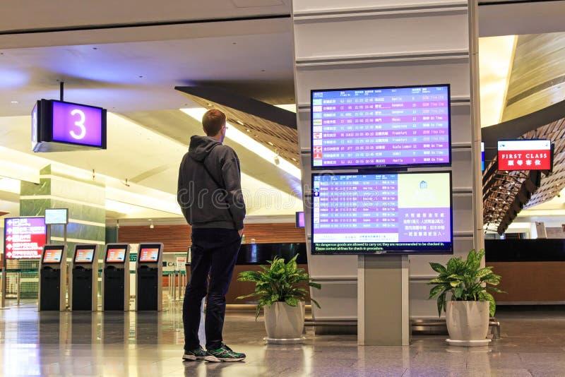 Bemannen Sie das Stading vor einem Flug-Informations-Brett innerhalb des internationalen Flughafens Taiwans Taoyuan stockbilder