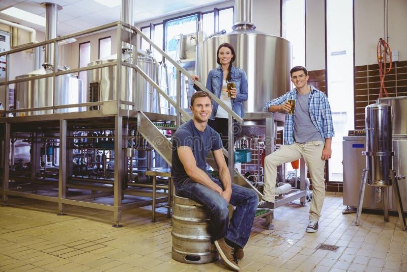 Bemannen Sie das Stationieren auf dem Fass und seinem Kollegen, die ein Glas Bier halten stockbild