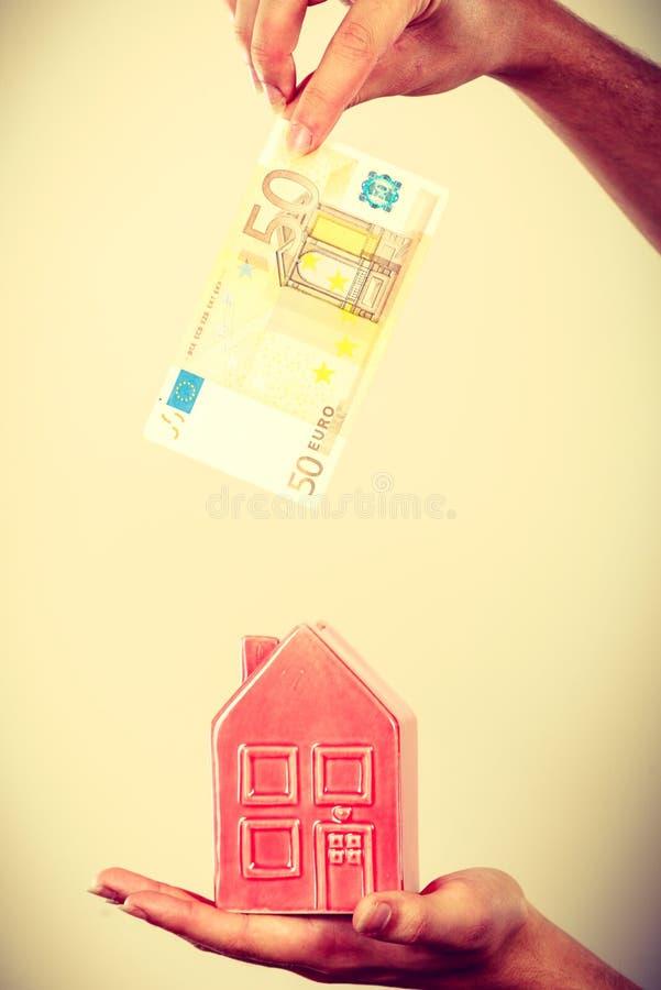 Bemannen Sie das Stecken des Geldes in Haus piggybank stockfotos