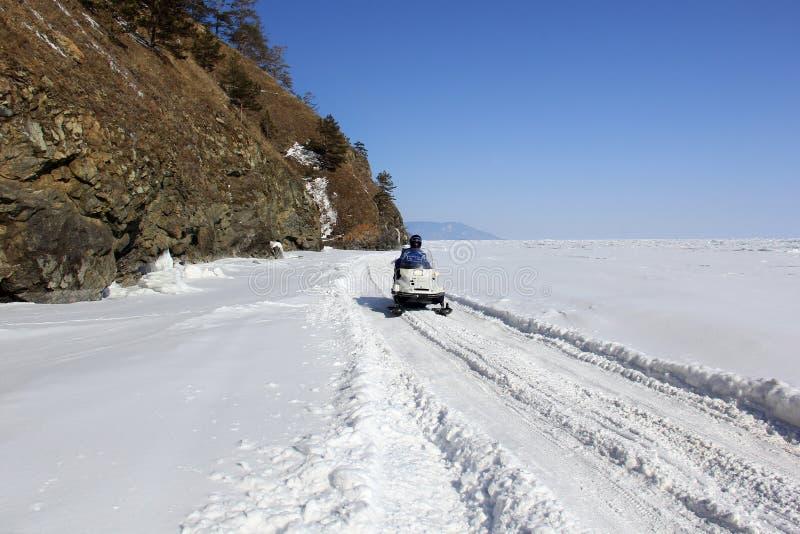 Bemannen Sie das Tragen eines Sturzhelms, der auf einem Schneemobil fahrung mitten in einem gefrorenen See sitzt stockbild