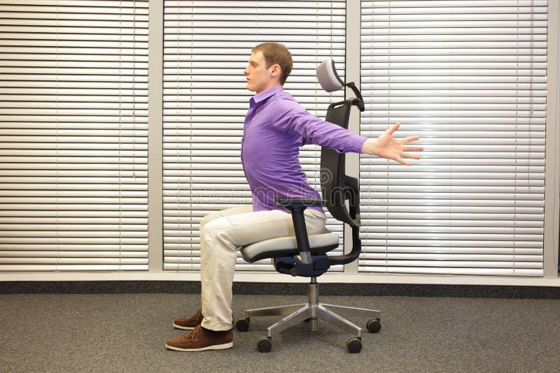 Bemannen Sie das Trainieren auf Stuhl im Büro, gesunden Lebensstil lizenzfreies stockfoto