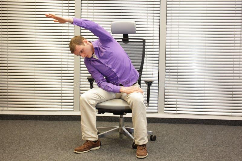 Bemannen Sie das Trainieren auf Stuhl im Büro, gesunden Lebensstil stockfotografie