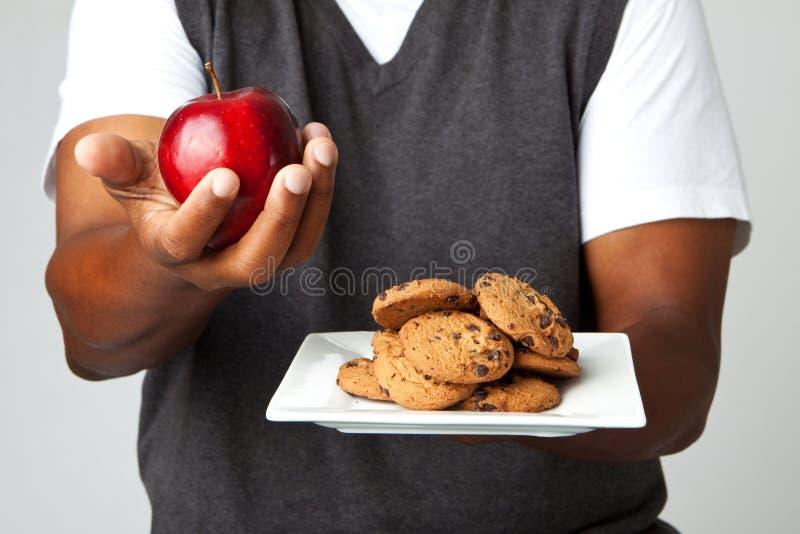 Bemannen Sie das Treffen von Entscheidungen des Essens von gesunden Versen ungesund lizenzfreie stockbilder