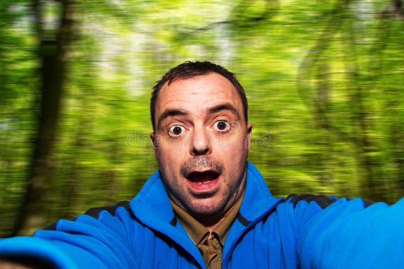 Bemannen Sie das Unterhaltungsselfie, das lustiges Gesicht auf unscharfem Hintergrund zieht lizenzfreies stockbild
