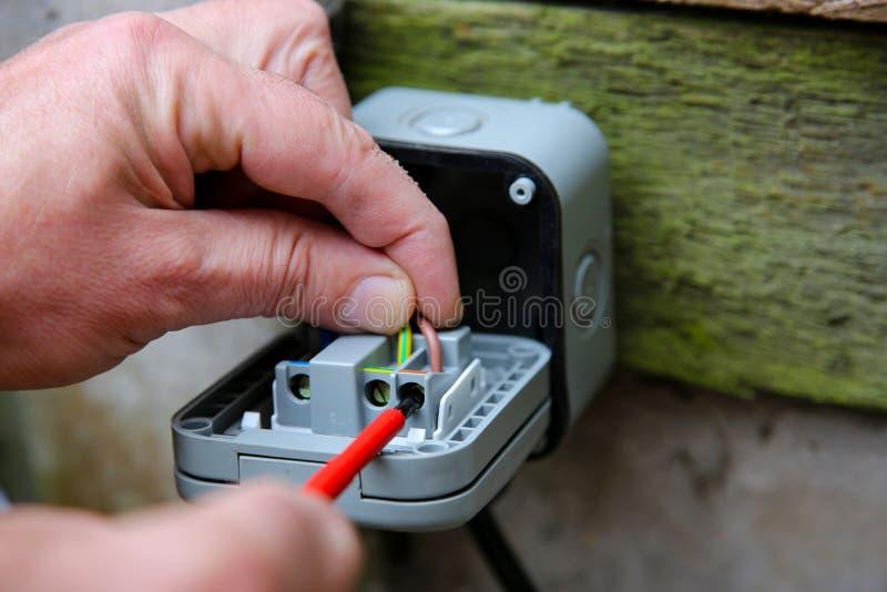 Bemannen Sie das Verdrahten eines Sockels unter Verwendung eines elektrischen Schraubenziehers lizenzfreie stockbilder