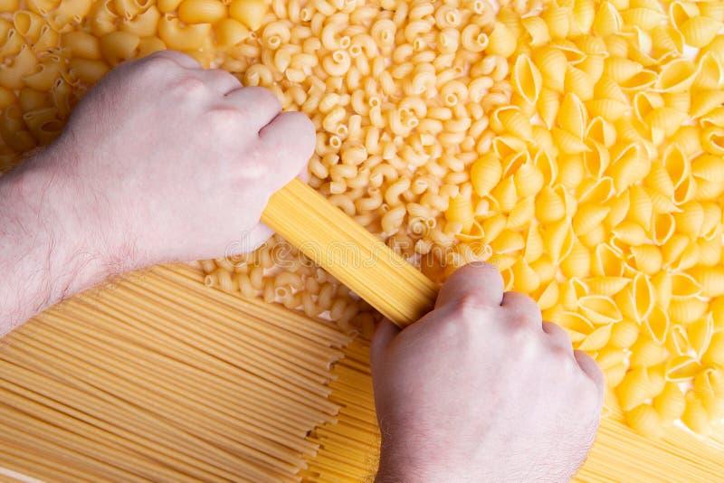 Bemannen Sie das Versuchen, Brunch von Spaghettis mit den Händen zu brechen lizenzfreie stockbilder