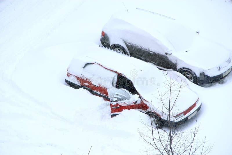 Bemannen Sie das Versuchen, sein Auto von der schneebedeckten Gefangenschaft freizugeben Geparkte Autos abgedeckt mit Schnee lizenzfreie stockbilder