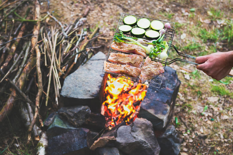 Bemannen Sie das Vorbereiten des Abendessens auf Lagerfeuer, kampierende Ferien des Abenteuerlebensstils lizenzfreies stockbild