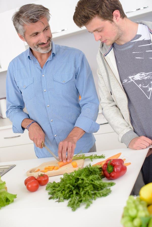 Bemannen Sie das Vorbereiten des jüngeren Mannes des Gemüses, der an zweifelhaft schaut stockfotografie
