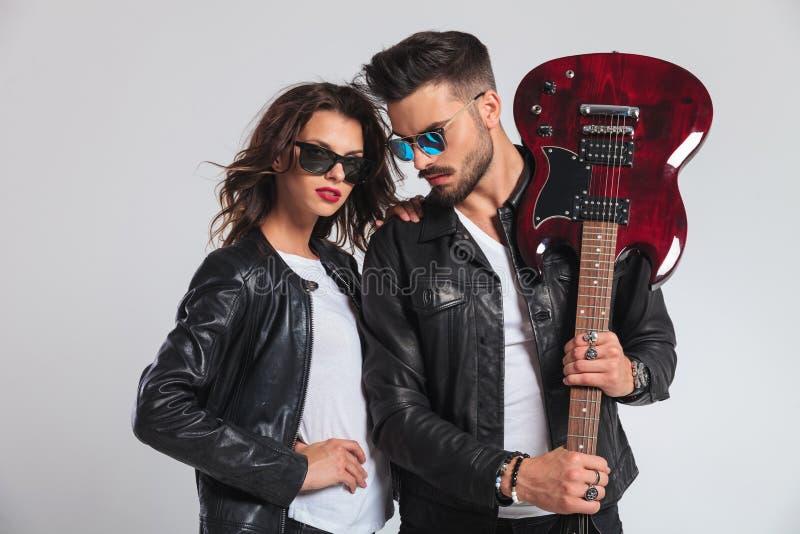 Bemannen Sie das Zeigen seiner E-Gitarre mit Frau durch seine Seite lizenzfreies stockfoto