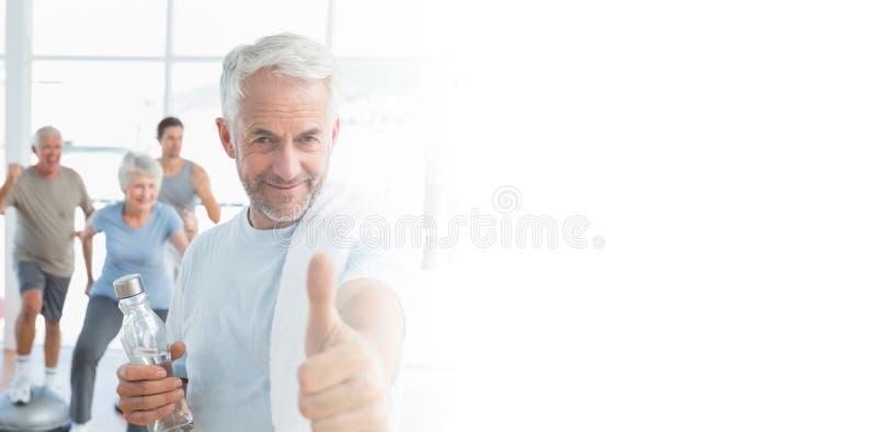Bemannen Sie das Zeigen von Daumen herauf Zeichen mit den Leuten, die im Hintergrund trainieren lizenzfreie stockfotos