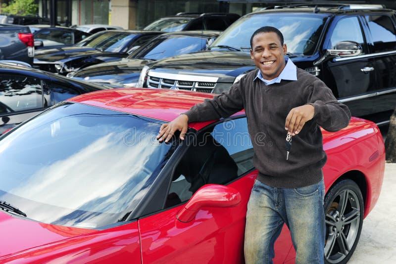 Bemannen Sie das Zeigen von Taste des neuen roten Sportautos stockfoto