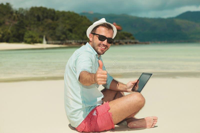 Bemannen Sie Daumen aufgeben beim Sitzen auf dem Strand mit ipad stockfotos
