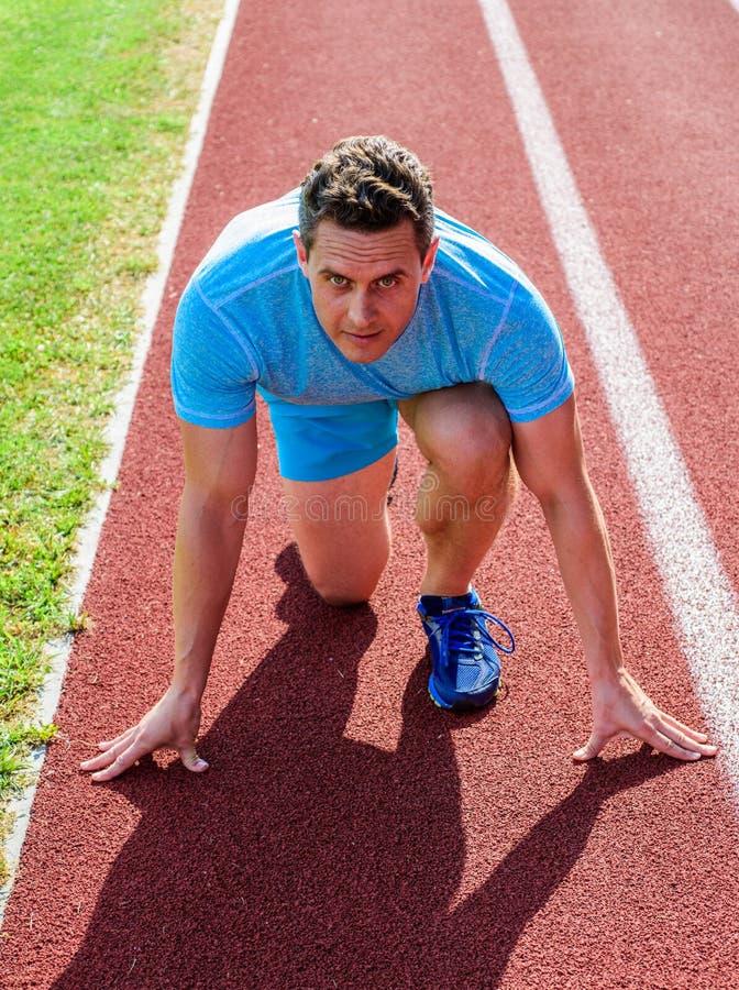 Bemannen Sie den Athleten, der auf das laufende Rennen gerichtet wird, das bereit ist zu gehen Starke niedrige Position des Läufe lizenzfreie stockfotografie