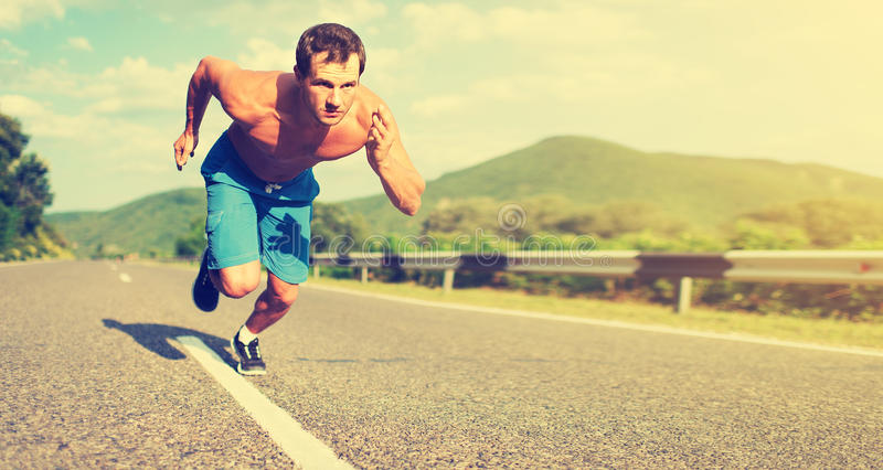 Bemannen Sie den Athleten, der auf der Natur bei Sonnenuntergang läuft stockfoto
