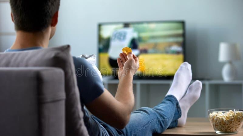 Bemannen Sie den aufpassenden amerikanischen Fußball, der Snäcke auf Couchhaus, Wochenendenfreizeit isst lizenzfreie stockfotografie