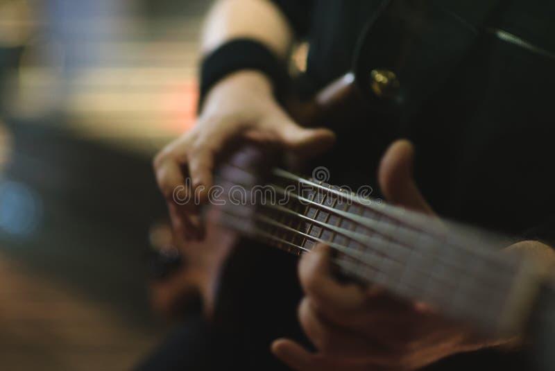 Bemannen Sie den Bass-Gitarristen, der elektrische Gitarre auf Konzertstadium spielt lizenzfreie stockbilder