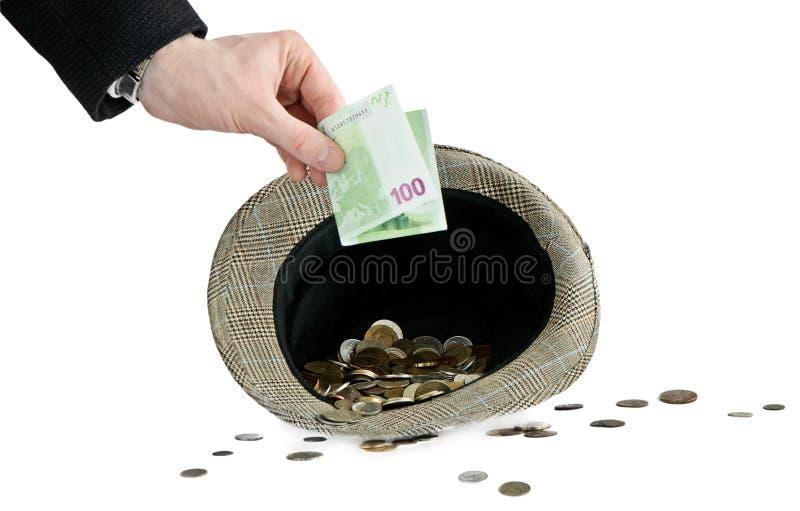 Bemannen Sie den Einsatz eines Geldes in Hut stockbild