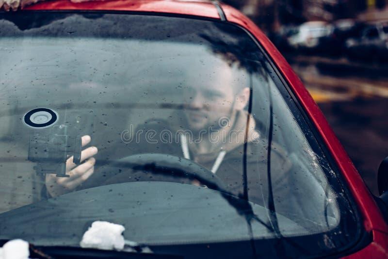Bemannen Sie den Fahrer, der intelligentes Telefon im Auto, modernes Internet-Technologiekommunikationskonzept verwendet lizenzfreie stockfotografie
