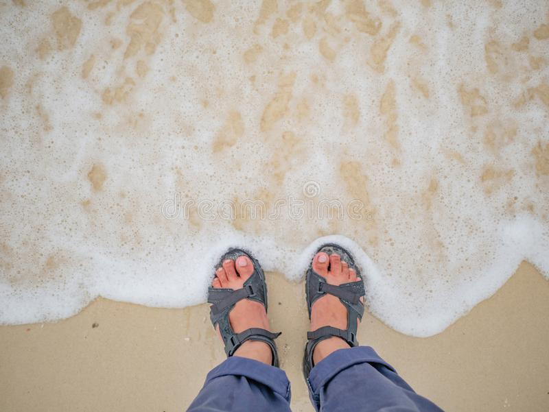 Bemannen Sie den Fuß, der auf dem Strand in der Ferienzeit steht lizenzfreies stockbild