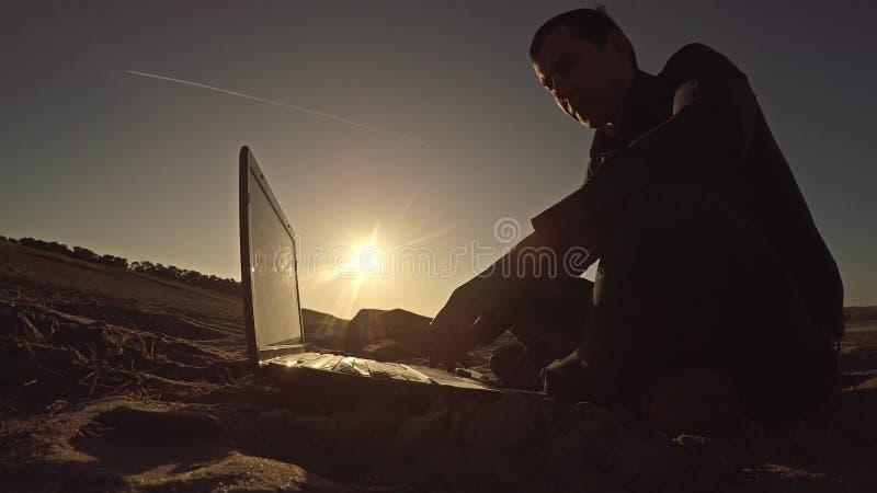 Bemannen Sie den Geschäftsmannfreiberuflerlaptop, der hinter dem Sitzen auf freiberuflich tätig seiendem Schattenbild des Strande stockbilder